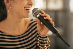 Closeup on woman singing with microphone. Closeup on happy young woman singing with microphone Stock Image