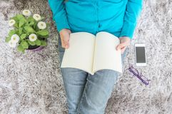 Closeup asian woman sitting on gray carpet at floor in the house textured background for read a book in relax time with artificial Stock Images
