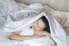 Closeup asian woman sleep on bed under blanket in bedroom background in the morning royalty free stock photos