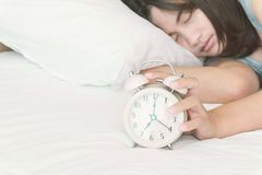 Closeup woman sleeping on the bed with alarm clock for wake up t royalty free stock image