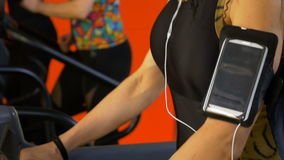 Closeup of woman with smartphone arm strap training on gym treadmill. Racetrack stock footage