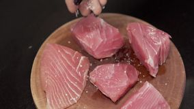 Fresh and uncooked tuna with salt. Slow motion closeup. Closeup woman sprinkles salt of fresh fillet tuna. Healthy food. Raw tuna with salt and papper. Big stock video