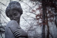 Closeup of woman stone statue. Front view closeup detail of dark woman stone statue covering her breasts with one hand with bare trees branches in the background Royalty Free Stock Photography