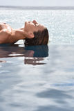 Closeup of woman sunbathing by the infinity pool Royalty Free Stock Image
