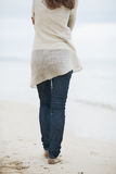 Closeup on woman in sweater walking on lonely beach Royalty Free Stock Photography