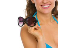 Closeup on woman in swimsuit holding sunglasses Royalty Free Stock Images