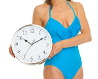 Closeup on woman in swimsuit showing clock Royalty Free Stock Photography