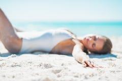 Closeup on woman in swimsuit sunbathing on sandy beach Stock Image