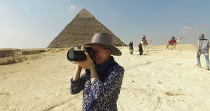 closeup of woman taking photos at Giza pyramids complex
