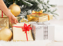 Closeup on woman taking present box under christmas tree Stock Images