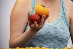 Closeup of woman in tank top holding two heirloom tomatoes in her hand at farmers market - unrecognizable stock photos