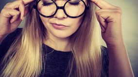 Closeup of woman thinking face expression. Intellectual expressions, being focused concept. Closeup of attractive woman wearing big eyeglasses thinking face royalty free stock photos