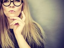 Closeup of woman thinking face expression. Intellectual expressions, being focused concept. Closeup of attractive woman wearing big eyeglasses thinking face stock images