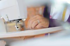 Closeup woman threading needle on sewing machine Stock Photography