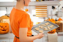 Closeup on woman with tray of uncooked Halloween biscuits Stock Photos