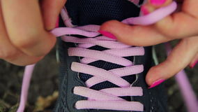 Closeup of woman tying running shoe in park stock footage
