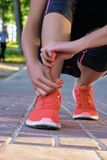 Closeup woman tying shoe laces. Street runner getting ready for training. royalty free stock photos