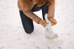 Closeup on woman tying shoelaces in gloves outdoors Royalty Free Stock Photo