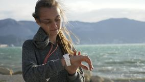 Closeup woman using smart sport running watch on the beach. Closeup woman in hoodie using smart sport running watch on the beach. Girl pushing buttons on the stock video footage