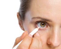 Closeup on woman using white eye liner Royalty Free Stock Images