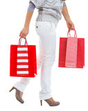 Closeup on woman walking with red shopping bags Royalty Free Stock Photos
