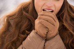 Closeup on woman warming hands with breathe in winter outdoors. Energy-filling and exciting winter weekends in the mountains. Closeup on woman warming hands with Stock Photos
