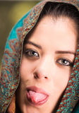 Closeup woman wearing blue, grey and brown coloured scarf covering head revealing face, holding tongue out Royalty Free Stock Images