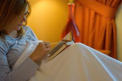 Woman reading in bed royalty free stock image