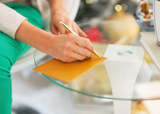 Closeup on woman writing on envelope near christmas tree Stock Photos