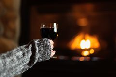 Woman sitting by fieldstone fireplace with glass of wine. Closeup of a womans hand holding a glass of wine by a romantic fieldstone fireplace stock photos