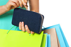 Closeup of womans hand with shopping bags opening wallet. Stock Image