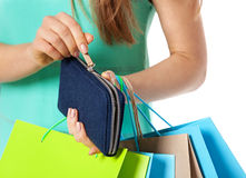 Closeup of womans hand with shopping bags opening wallet. Royalty Free Stock Photos
