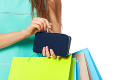 Closeup of womans hand with shopping bags opening wallet. Stock Photography