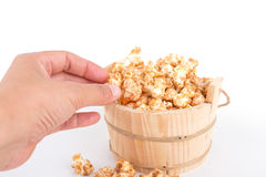 Closeup of a womans hand taking some popcorn from a wood basket Royalty Free Stock Photo