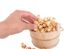 Closeup of a womans hand taking some popcorn from a wood basket Stock Image