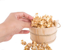Closeup of a womans hand taking some popcorn from a wood basket Stock Photography