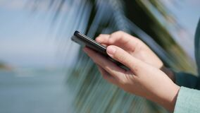 Womans hands using smartphone over background sea and palm trees. Girl touching screen. Closeup womans hand using smartphone over background sea and palm trees stock footage