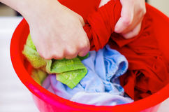 Closeup womans hands handwashing clothes in red plastic washbucket, scrubbing and squeezing fabrics, laundry housework concept Royalty Free Stock Image