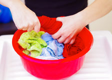 Closeup womans hands handwashing clothes in red plastic washbucket, scrubbing and squeezing fabrics, laundry housework concept Stock Photos