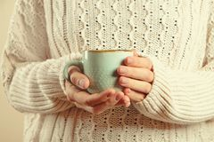 Closeup of a womans hands holding a mug with drink. Blue mug in womans hands on knit sweater background Royalty Free Stock Image