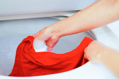 Closeup womans hands putting red clothing into washing machine, laundry housework concept Stock Photos