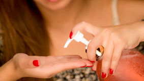 Closeup womans hands squeezing cream from bottle into palm of hand Royalty Free Stock Photo