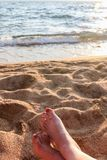 Closeup of Womans Legs and Feet at the Beach Stock Images