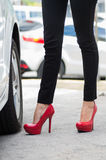 Closeup womans legs wearing black jeans and red stilettos standing outside car door, other cars background, female. Driver concept Royalty Free Stock Image
