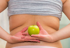 Closeup womans lower back with shirt lifted up, wearing jeans, holding apple between hands, weightloss concept Royalty Free Stock Images