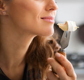 Closeup of womans mouth getting ready to eat piece of Camembert Royalty Free Stock Images