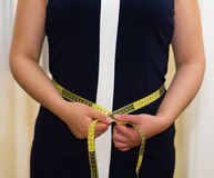 Closeup womans stomach wearing blue dress, holding measure band between hands, weightloss concept Royalty Free Stock Images