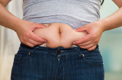 Closeup womans stomach wearing jeans, grabbing onto excessive fat using fingers, belly button revealed, weightloss Royalty Free Stock Photography