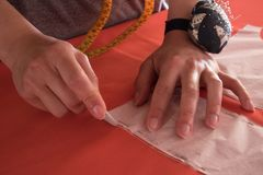 Closeup of Women fashion designer`s hands marking with chalk on cloth in workshop.  royalty free stock photos