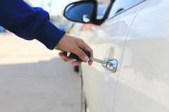 Closeup Women hand holding car key to unlocking or opening car door stock image